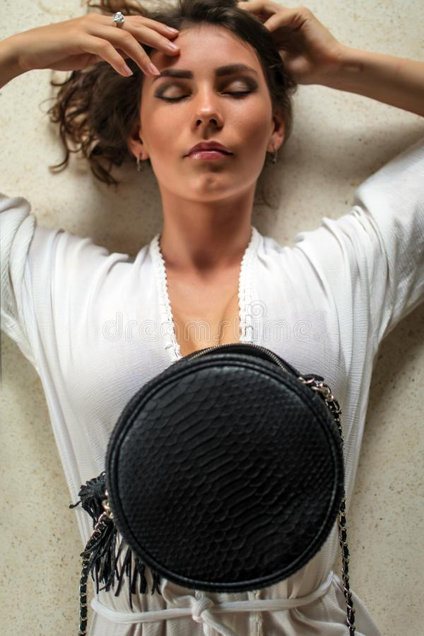Over head portrait view of an beautiful young woman laying down in her expensive villa with luxuty python bag. Have curly hair,. Over head portrait view of an stock image