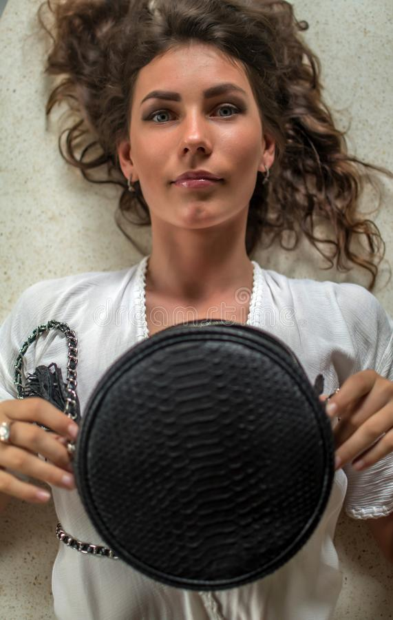 Over head portrait view of an beautiful young woman laying down in her expensive villa with luxuty python bag. Have curly hair, stock photo