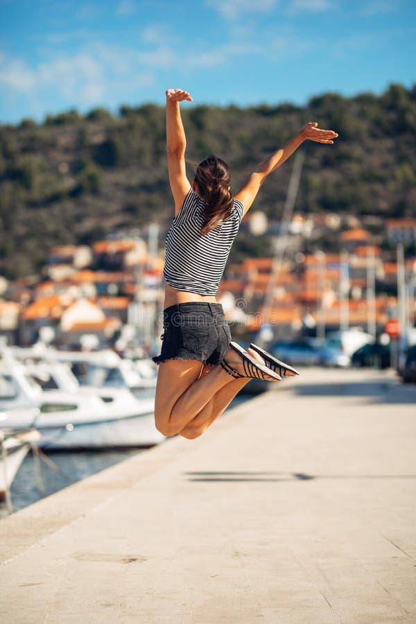 Over het weggegaane gelukkige vrouw springen in de lucht uit geluk De tijdconcept van de vakantie Opwinding van de kust de kustva stock foto's