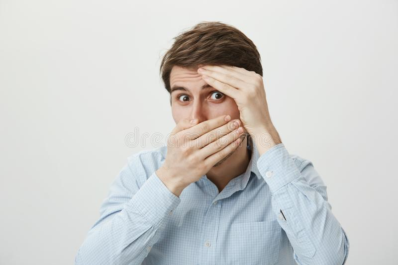 Is it over now. Portrait of scared and shocked young attractive man covering face with hands as if hiding or feeling. Fear, peeking at camera through hole royalty free stock image