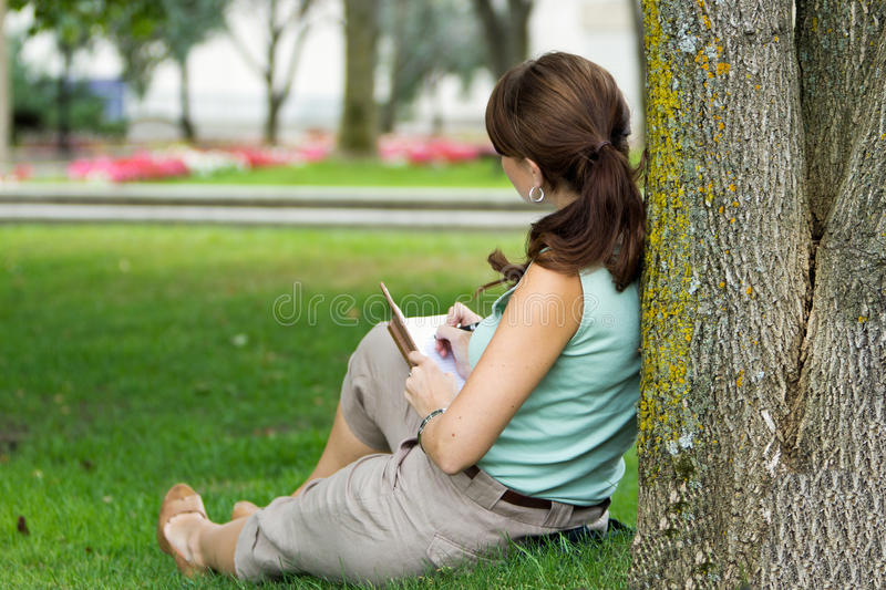 Over should look of young attractive fresh woman at the park writes in notebook journal stock photo