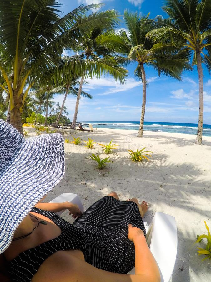 Over shoulder POV: woman in hat and dress on sun lounger on vacation at idyllic tropical beach with palm trees at Lefaga, Upolu I stock photo