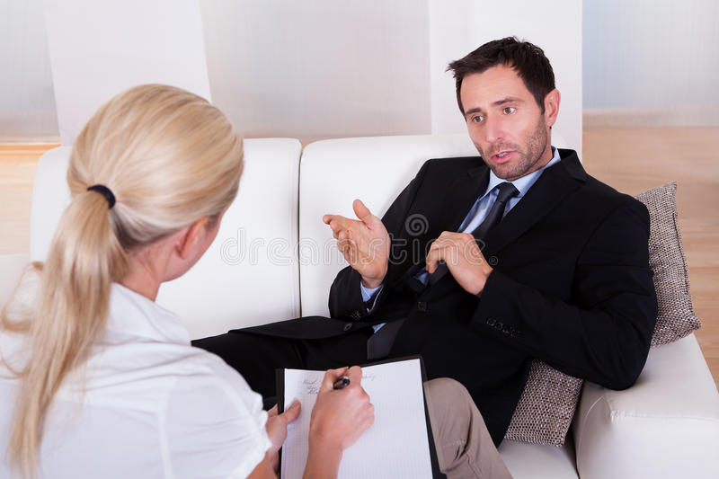 Man talking to his psychiatrist. Over the shoulder view of a business men reclining comfortably on a couch talking to his psychiatrist explaining something royalty free stock images