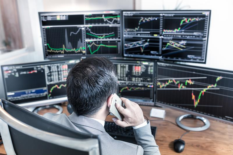 Over the shoulder view of computer screens and stock broker trading online. Over the shoulder view of computer screens ful of charts and data analyses and stock stock photos