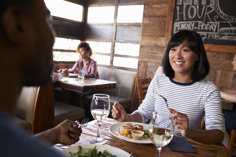 Over shoulder view of couple having lunch in a restaurant royalty free stock photos