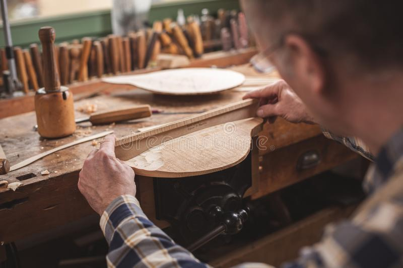 Instrument maker at work at his workbench. Over shoulder view of an instrument maker checking his workpiece with a wooden template. Located inside a rustic stock photography