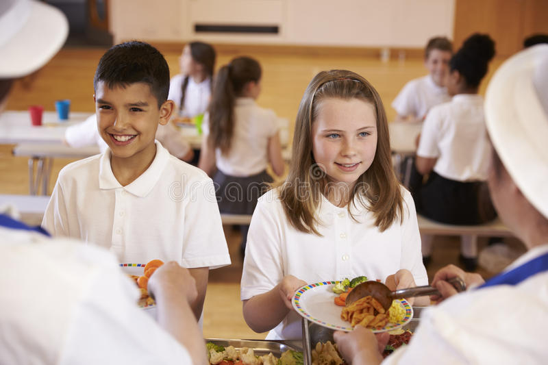 Over shoulder view of kids being served in school cafeteria royalty free stock photography