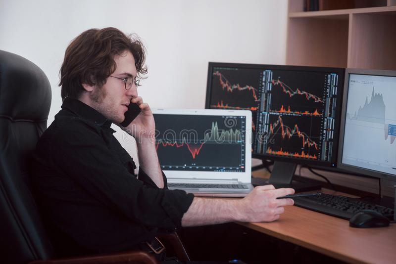 Over the shoulder view of and stock broker trading online while accepting orders by phone. Multiple computer screens ful. Of charts and data analyses in stock photos