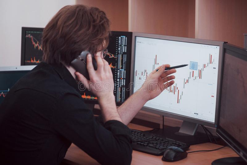 Over the shoulder view of and stock broker trading online while accepting orders by phone. Multiple computer screens ful. Of charts and data analyses in stock image