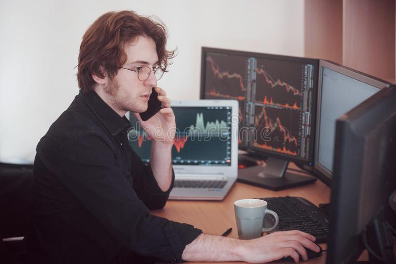 Over the shoulder view of and stock broker trading online while accepting orders by phone. Multiple computer screens ful. Of charts and data analyses in royalty free stock images