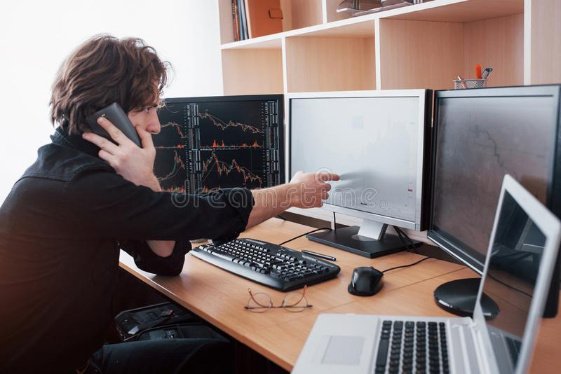 Over the shoulder view of and stock broker trading online while accepting orders by phone. Multiple computer screens ful. Of charts and data analyses in royalty free stock photo