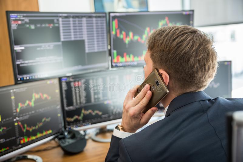 Over the shoulder view of stock broker trading online, talking on mobile phone. Over the shoulder view of and stock broker trading online while accepting orders stock photography