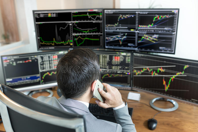 Over the shoulder view of stock broker trading online, talking on mobile phone. Over the shoulder view of and stock broker trading online while accepting orders royalty free stock images