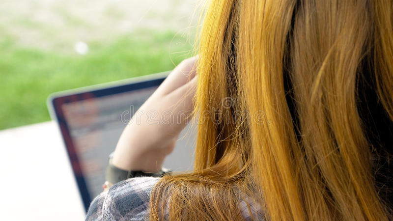Over shoulder of young woman with red hair. View over shoulder of young woman with red hair using laptop at summertime. Working on pc outdoors royalty free stock images