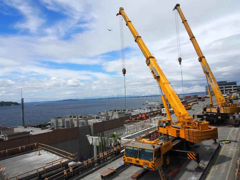 Over Size Load portable Barnhart Cranes works on the tear down of State Route 99 along Seattle seaboard with bird in the air stock images