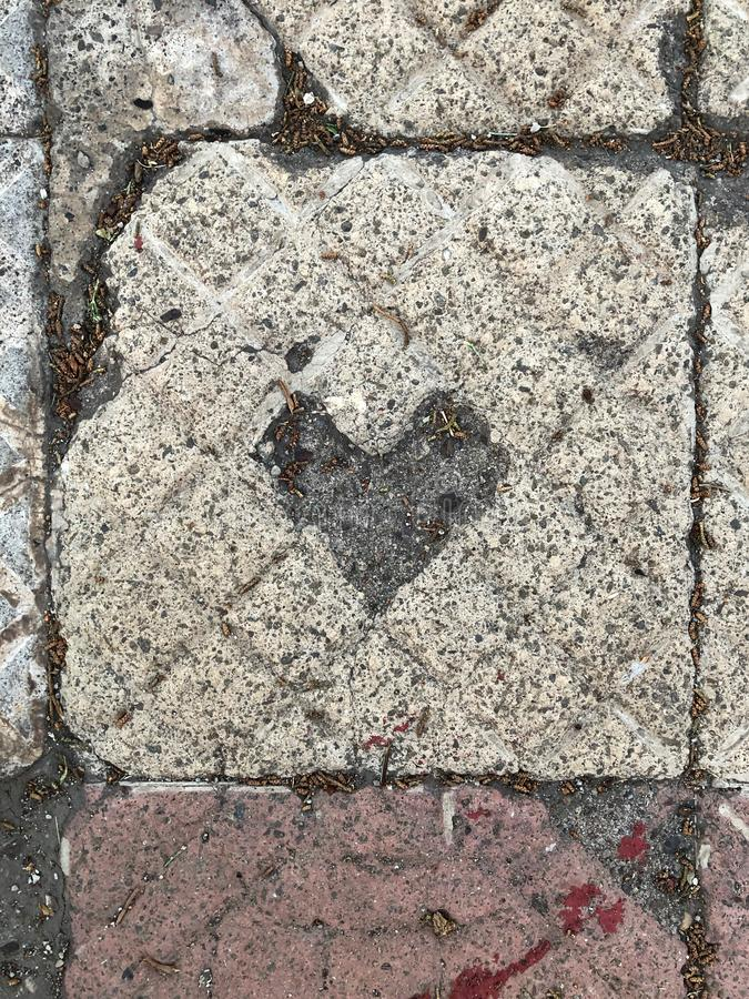 Carved tile with heart shape by time. Over time the hardness gave way to love and his feelings, symbol stock image
