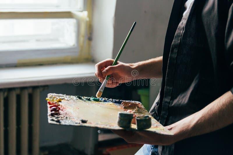 Over van het venster houdt de kunstenaar een palet met verven en een borstel en gaat op canvas schilderen stock fotografie
