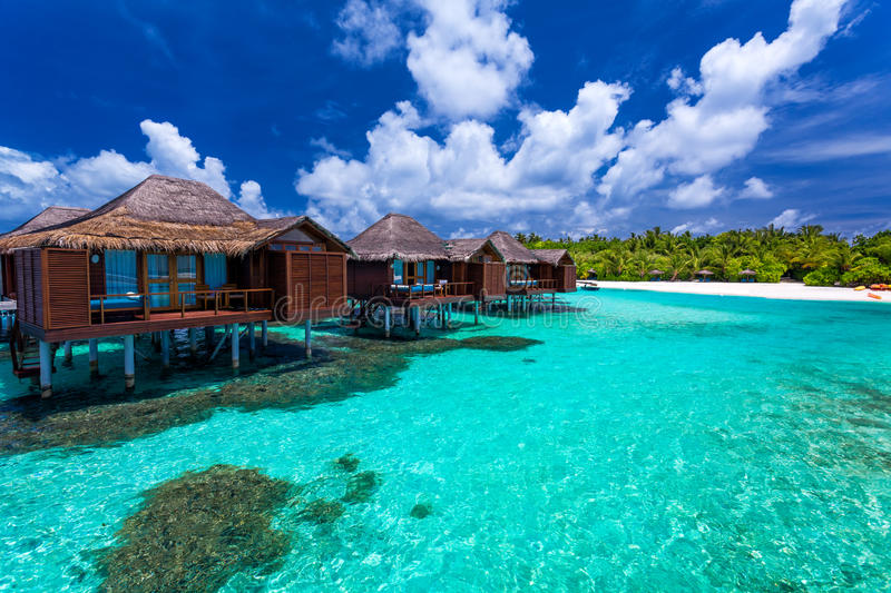Over water bungalows with steps into green coral lagoon. Over water bungalows with steps into amazing green lagoon with coral stock photos