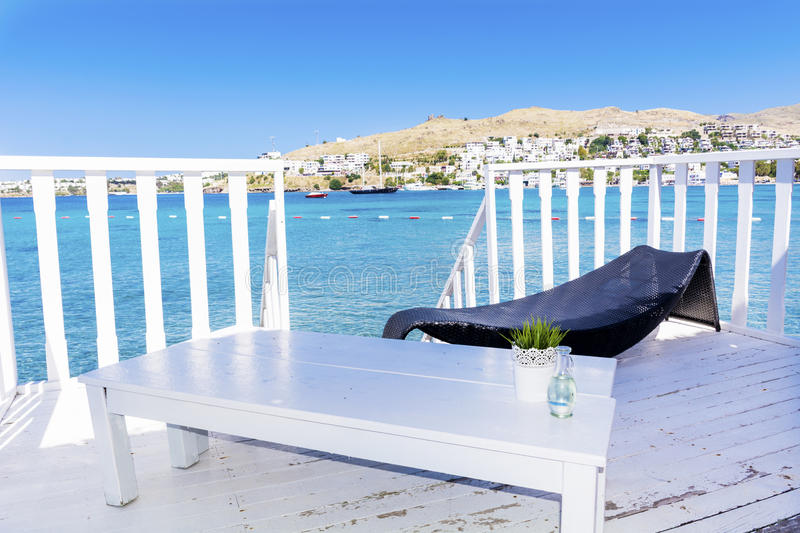 Over water wooden bungalow with sunbed and table on a sea view royalty free stock photography