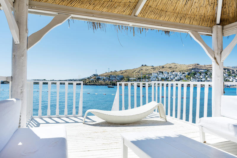 Over water wooden bungalow with white sunbed royalty free stock images