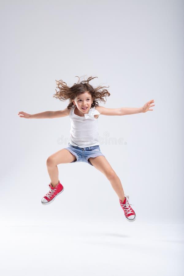 Overactief meisje die in de lucht springen stock afbeeldingen