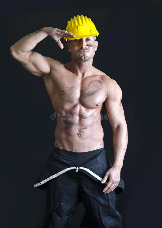 Overall och hardhat för Shirtless muskulös byggnadsarbetare bärande royaltyfri foto