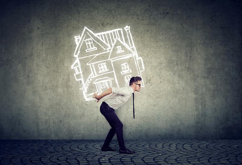 Overburdened business man carrying a house royalty free stock photo