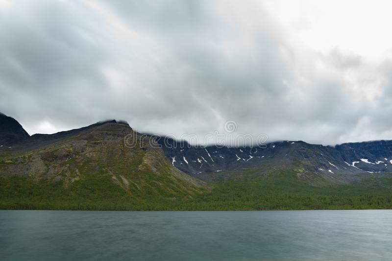 Overcast cloudy sky over lake and mountains Khibiny. royalty free stock image