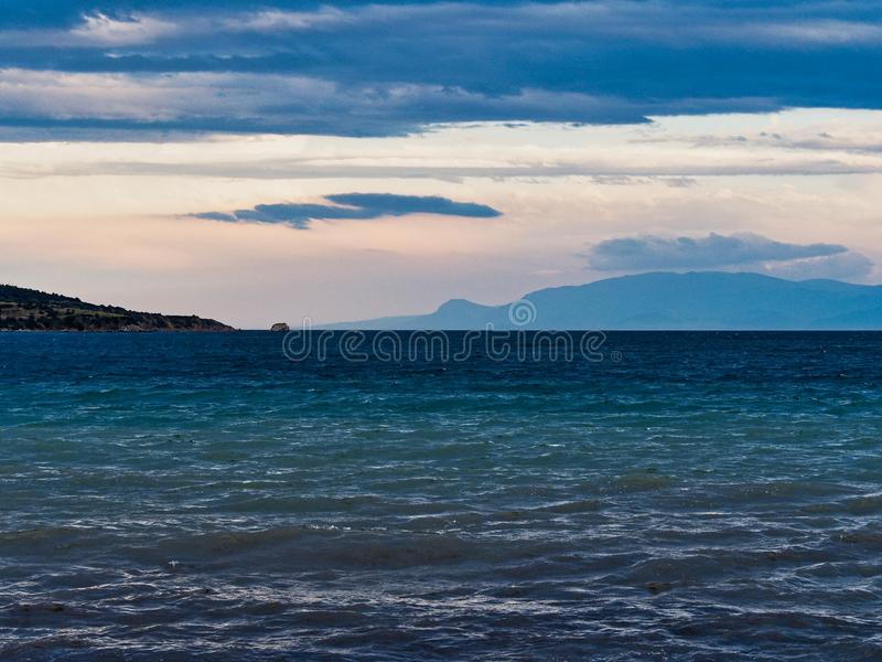 Overcast Early Morning View Over Gulf of Corinth Bay to Peloponnese Mountains. Choppy water in a north side Gulf of Corinth bay, Ormos Lemonias, literally Bay of royalty free stock images