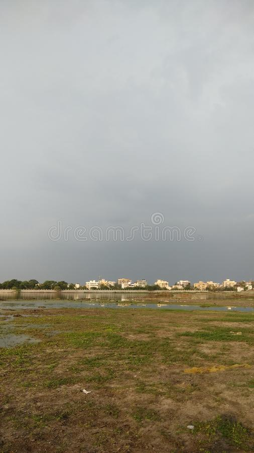 Overcast monsoon sky buildings and a wetland. During july royalty free stock photography