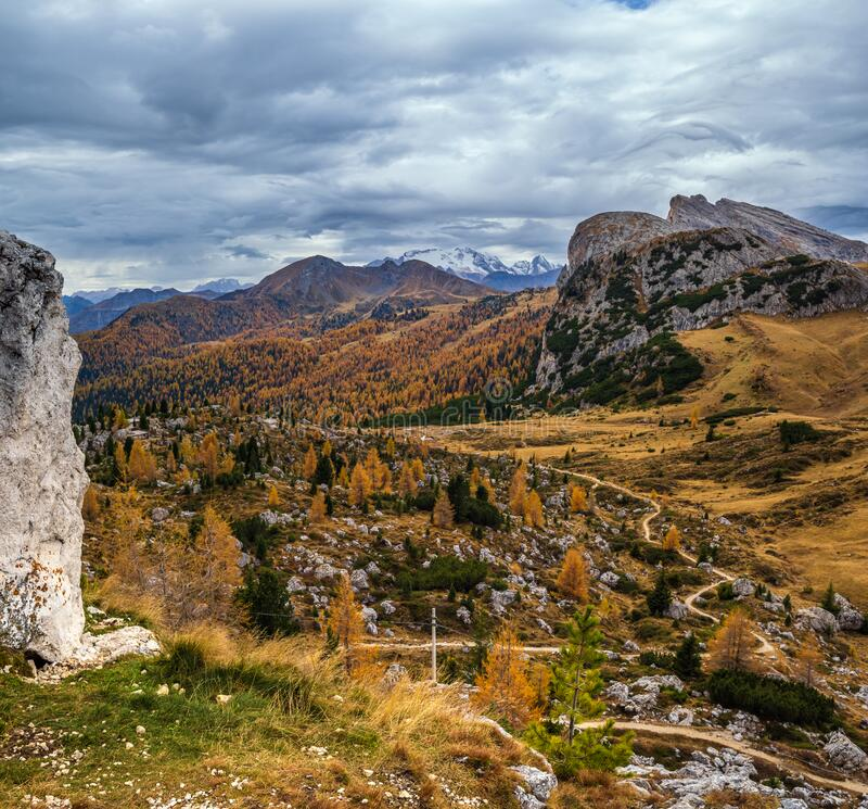 Overcast morning autumn alpine Dolomites mountain scene. Peaceful Valparola Path view, Belluno, Italy. Snowy Marmolada massif and. Overcast morning autumn alpine stock image
