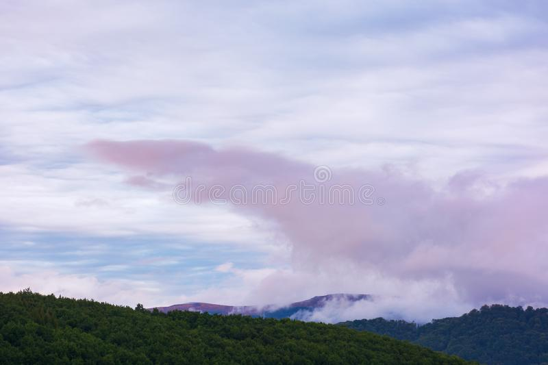 Overcast purple sky at dawn. Overcast purple sky above the mountain ridge at dawn. beautiful nature background royalty free stock photos