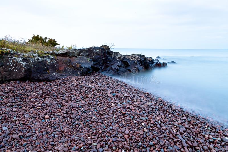 Lake Superior rocky shore in Northern Michigan. Overcast sky and calm water of the Lake Superior stock photography