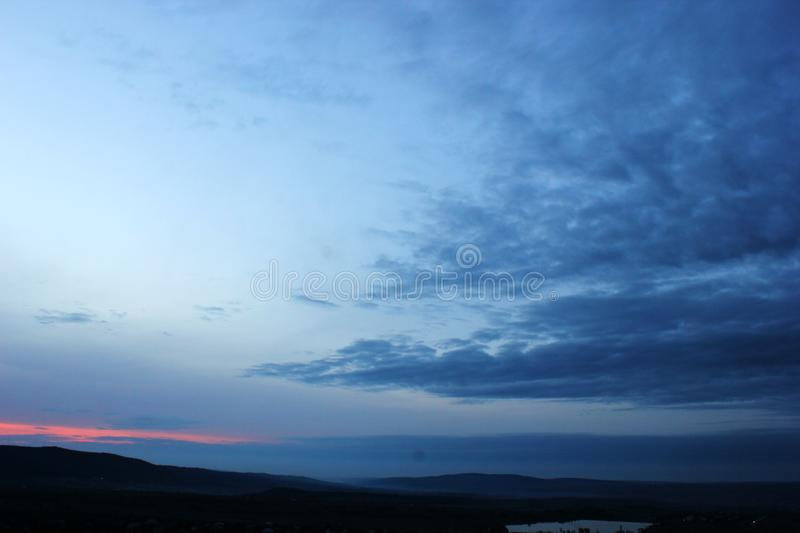 Overcast sky, mountains in the distance,. Pink, scarlet sunset, clouds and gray, dark clouds, rainy weather in autumn and spring, natural phenomena, weeping stock photos
