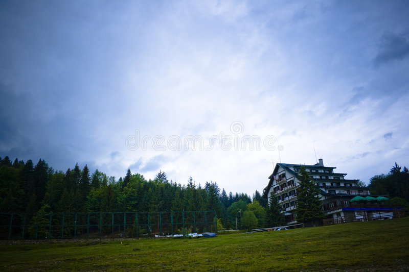 Overcast Sky over Mountain Lodge. Isolated mountain lodge under an overcast sky. Dark, stormy atmosphere royalty free stock images