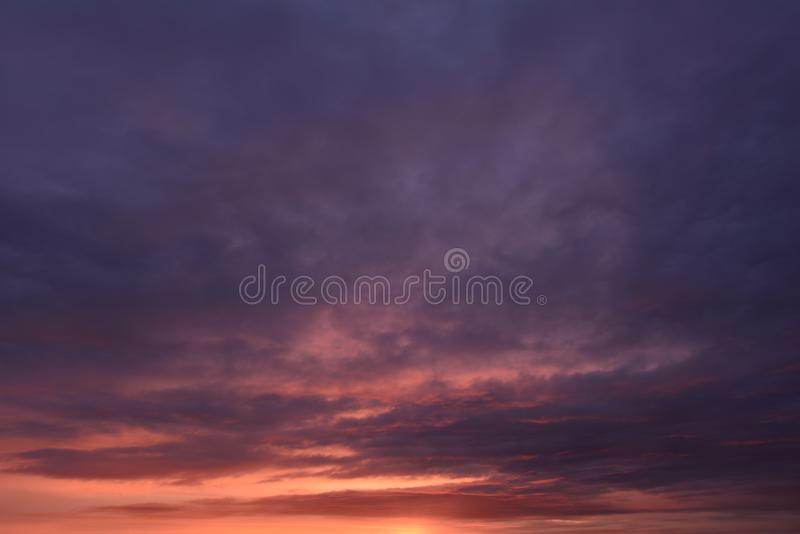 Overcast sky  in  thunderclouds in the fiery lava of sunlight at sunset royalty free stock photo