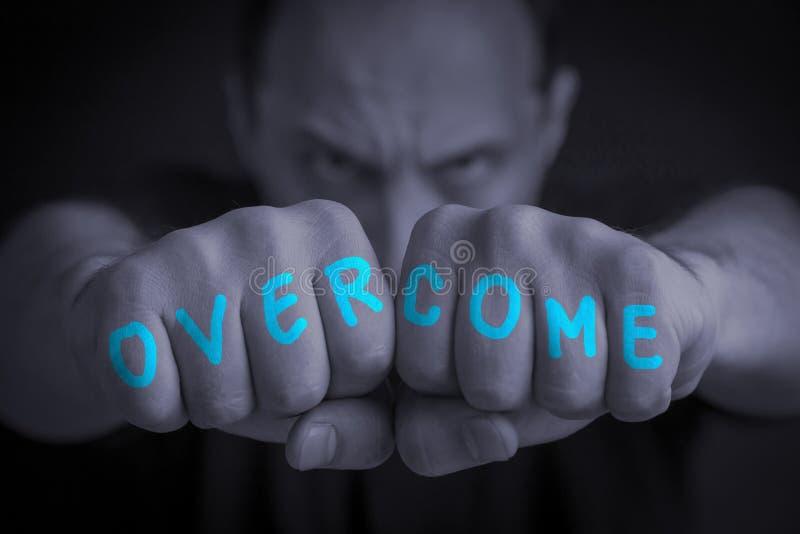 OVERCOME escrita en puños enojados de los man's foto de archivo libre de regalías