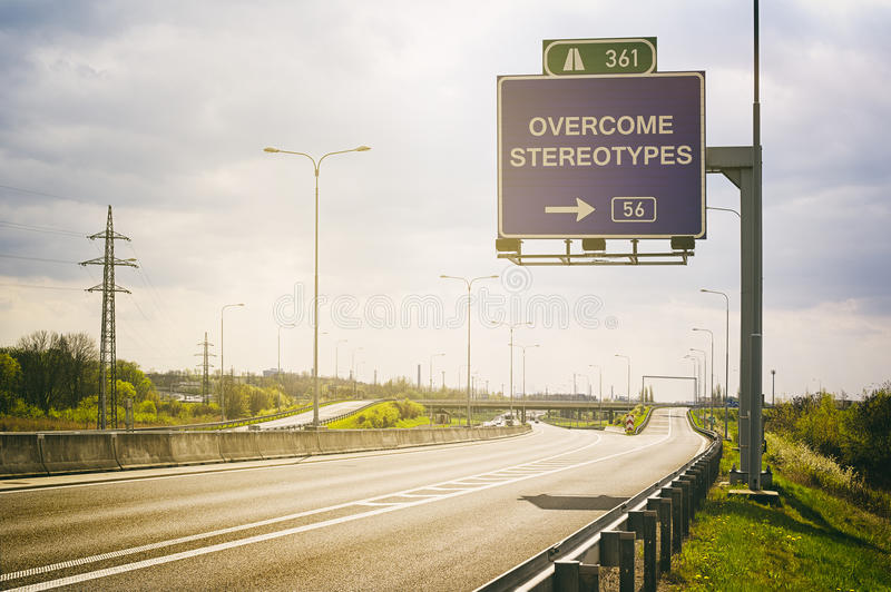 Overcome stereotypes and generalization. Empty highway and traffic sign above it. Text Overcome Stereotypes - appeal to avoid stereotypes, prejudice and stock photography