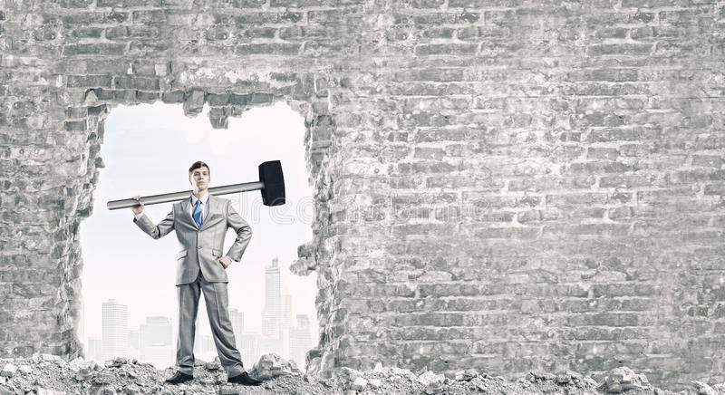 Overcoming challenges. Young businessman with big hammer against wall royalty free stock images