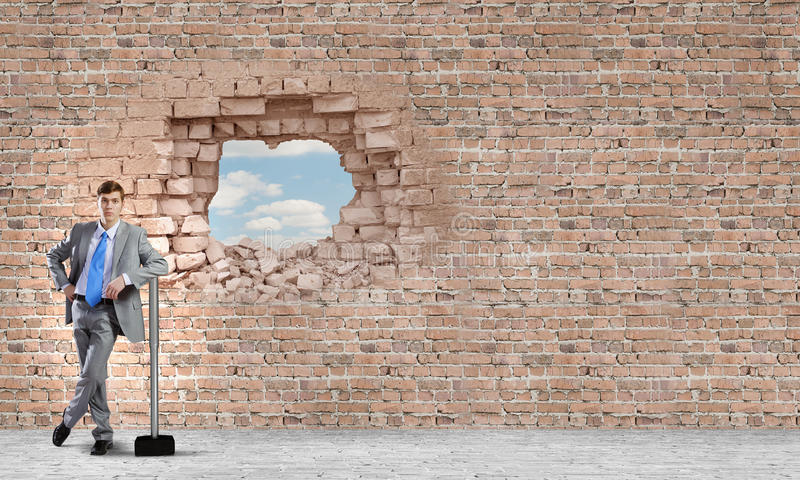 Overcoming challenges. Young businessman with big hammer against wall stock photography