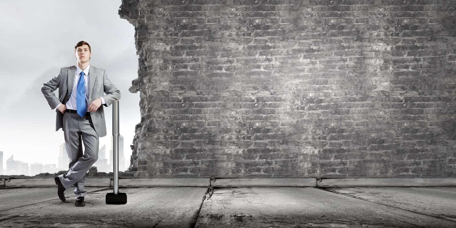 Overcoming challenges. Young businessman breaking cement wall with hammer royalty free stock images