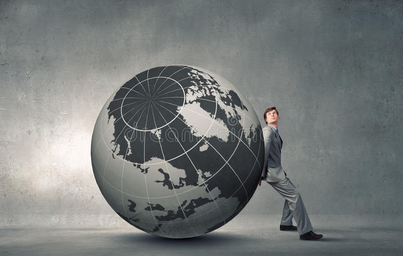 Overcoming challenges. Young businessman pushing huge digital Earth planet stock image