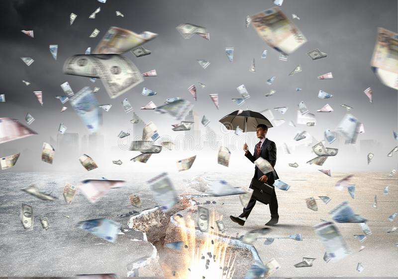 Overcoming the difficulties. Mixed media. Businessman with umbrella and suitcase walking on cracked road. Mixed media royalty free stock image