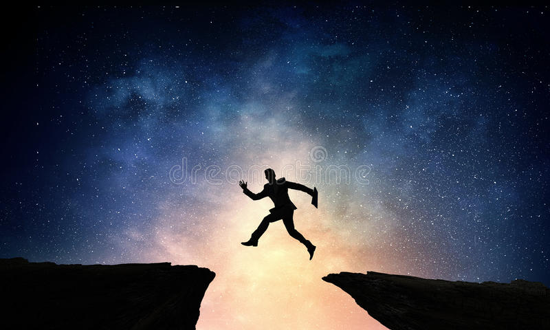 Overcoming life difficulties . Mixed media. Silhouette of businessman jumping over hill gap against night sky background stock photos