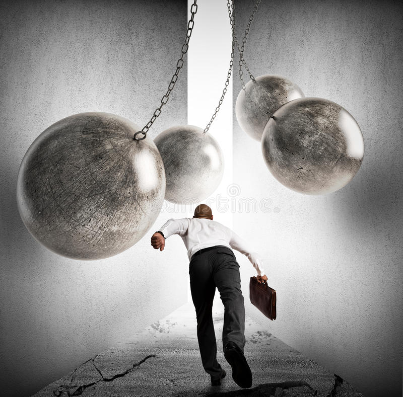 Overcoming obstacles to achieving success. Businessman runs between iron balls. Overcoming obstacles to achieving success royalty free stock photo