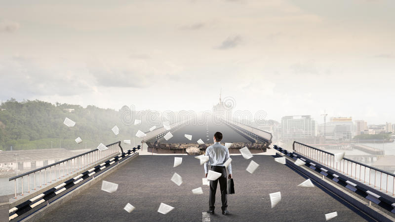 Overcoming problems and difficulties . Mixed media. Businessman standing on edge of destructed bridge. Mixed media royalty free stock images