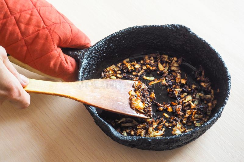 Overcooked onion in a pan. A bad kitchen. The concept of harmful food and carcinogens. Overcooked onion in a pan. A bad kitchen. The concept of harmful food and royalty free stock photos