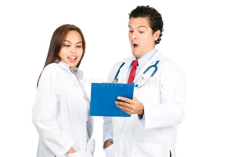Overdreven Mannelijke Vrouwelijke Artsen Team Records H royalty-vrije stock afbeeldingen