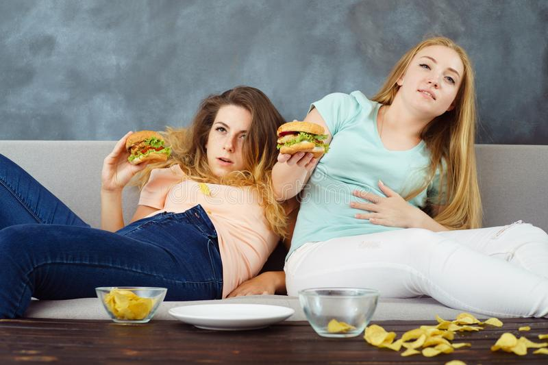 Overeaten women lying at coach eating fast food royalty free stock image