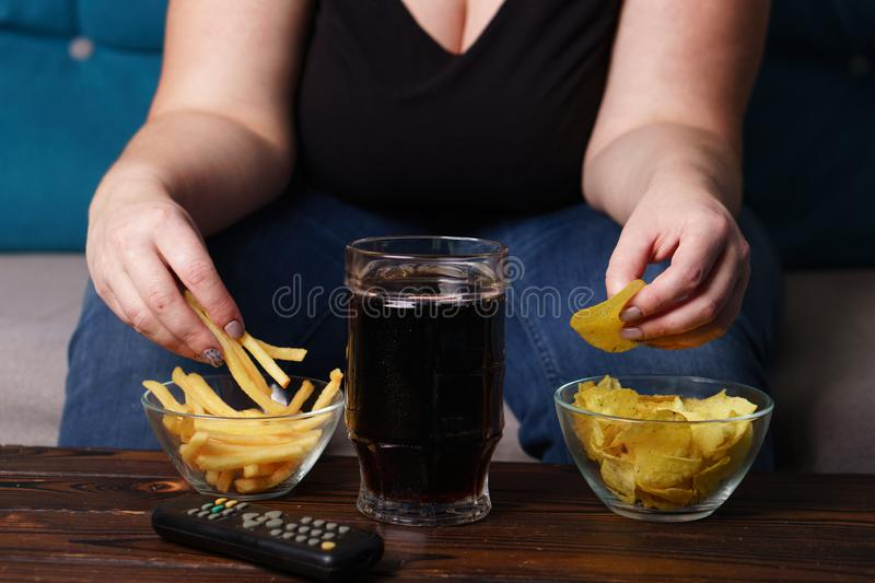 Overeating, sedentary lifestyle, bad habits. Food addiction, eating disorders. fat overweight woman sit on the coach with tv remote, junk food and beer royalty free stock images